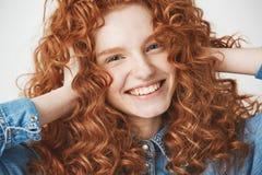 关闭年轻美丽的微笑姜女孩感人的头发看照相机 奶油被装载的饼干 免版税库存图片