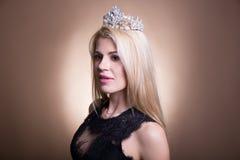 关闭年轻美丽的白肤金发的妇女画象黑礼服的 免版税库存图片