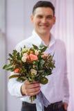 关闭给花的花束白色衬衣的年轻人作为惊奇,在玫瑰的焦点 免版税图库摄影