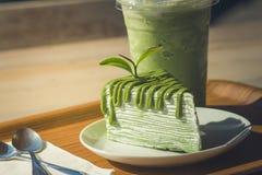 关闭绿茶蛋糕和matcha被冰的绿茶在木盘子 免版税库存照片