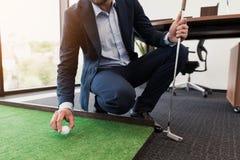 关闭 西装的一个人在办公室打高尔夫球 免版税库存照片
