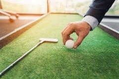 关闭 西装的一个人在办公室打高尔夫球 库存图片