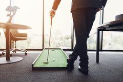 关闭 西装的一个人在办公室打高尔夫球 图库摄影