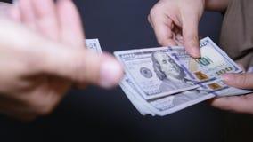 关闭付从计数一百元钞票的人的手的现金入妇女的手 股票视频