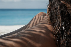 关闭说谎在与阴影的海滩的atrractive女孩 免版税图库摄影