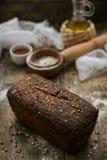 关闭说谎在木桌上的新鲜的棕色酥脆面包看法洒与面粉 免版税库存照片