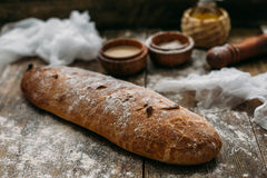 关闭说谎在木桌上的新鲜的棕色酥脆面包看法洒与面粉 库存图片