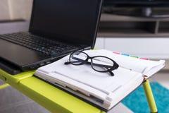 关闭说谎在膝上型计算机桌上的时髦的玻璃 库存照片