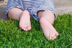 关闭 赤足愉快的儿童脚在绿草 健康生活方式 春天…上升了叶子,自然本底 查出的背面图白色 扁平足的概念,孩子 图库摄影