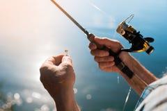 关闭 转动与在右手的一个卷轴,有诱饵的勾子在左手以水为背景 免版税图库摄影