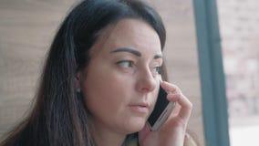 关闭-,美女谈话在坐在咖啡馆和看窗口的电话 股票录像
