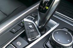 关闭BMW X5在黑皮革汽车内部的F15无线钥匙2017年 现代汽车内部细节 免版税库存照片
