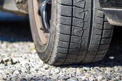 关闭car& x27; s冬天在石渣路的轮胎踩 免版税库存图片