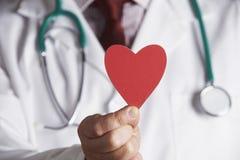关闭Holding Cardboard Heart医生 免版税库存图片