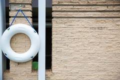 关闭lifebuoy,所有水抢救事故设备 白色lifebuoy在砖墙上 库存照片