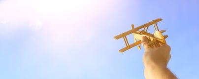 关闭man& x27; 拿着玩具飞机的s手反对日落天空 免版税库存图片