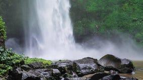 关闭Nungnung瀑布,击中水表面,在框架前面的一些巨大的湿岩石的落的水 醉汉绿色 股票视频