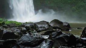 关闭Nungnung瀑布,击中水表面,在框架前面的一些巨大的湿岩石的落的水 醉汉绿色 股票录像