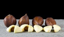 关闭salak果子切有在灰色石头的黑背景 库存照片