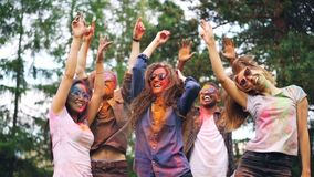 兴奋的男人和妇女跳舞获得乐趣在现代党,他们的面孔,并且衣裳用多色油漆盖 股票录像