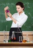 兴高采烈的化学教师检查圆锥形烧瓶 免版税库存图片