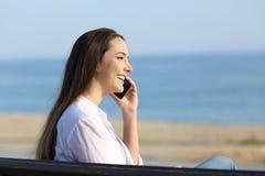 兴高采烈的夫人谈话在海滩的电话 免版税图库摄影