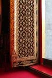 其中一个曼谷佛教寺庙的门,泰国,用被雕刻的和金黄花卉样式装饰 免版税库存图片