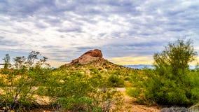 其中一座Papago公园红砂岩小山在菲尼斯亚利桑那附近的在多云天空下 库存图片