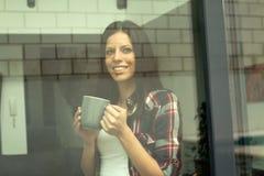 其次喝一个杯子cofee的俏丽的妇女窗口 免版税库存照片
