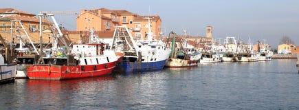其他船在Mediter的港停泊的红色捕鱼船 免版税库存照片