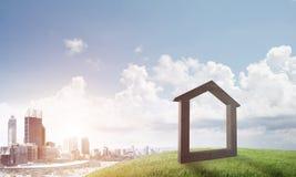 具体家庭标志的概念性图象在小山和自然风景的在背景 免版税图库摄影