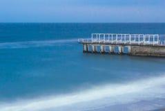 具体码头,有对此的木大厦的,洗涤由黑海的水 照片在长的曝光被拍了 图库摄影
