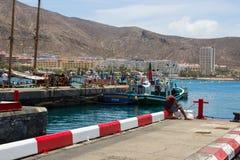 从具体跳船的唯一男性渔在Los的Cristianos拥挤小游艇船坞在Teneriffe海岛上的 库存图片