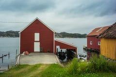 经典之作、红色挪威房子和小船 免版税库存照片