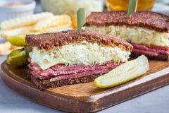 经典之作reuben三明治,供食用泡菜,土豆片,水平 免版税图库摄影