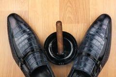 经典人的鞋子、烟灰缸和发怒的雪茄在木flo 免版税库存照片