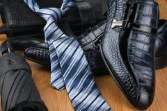 经典人的鞋子、领带、伞和袋子在木地板上 图库摄影