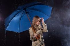 经典军用防水短大衣的妇女有伞的在雨中 免版税库存照片