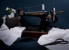 经典减速火箭的样式手工缝纫机准备好工作、剪刀,织品和老 库存图片