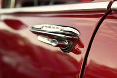 经典减速火箭的葡萄酒红色汽车 里面门把手 汽车大于1985年 免版税库存照片