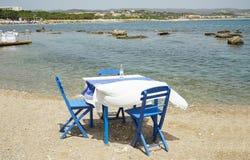 典型地希腊蓝色餐馆桌和椅子在海旁边 库存图片