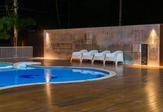 典型放松有游泳池的区域在豪华,热带手段在晚上 免版税图库摄影