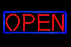 典型的'开放'在黑被隔绝的背景的餐馆霓虹灯广告 蓝色和红色霓虹灯广告 库存照片