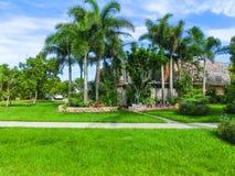 典型的佛罗里达家在有棕榈树、热带植物和花的乡下 免版税库存照片