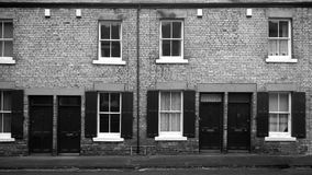 典型的北英国工人阶级露台的房子行的单色图象有走下去打开对街道的门的 库存图片