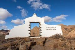 典型的在贝坦库里亚村庄附近的自治市标志白色曲拱门有沙漠山风景的在背景中, Fuerteventur 免版税库存图片