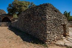 典型的小屋全景由与被围住的篱芭和晴朗的蓝天的石头制成,在Bories村庄,在戈尔代附近 库存照片