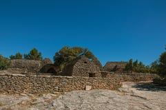 典型的小屋全景由与被围住的篱芭和晴朗的蓝天的石头制成,在Bories村庄,在戈尔代附近 免版税图库摄影