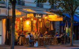 典型的巴黎人咖啡馆Le Parvis在晚上巴黎,法国找出下个著名Notre Dame大教堂 免版税库存图片