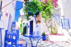 典型的希腊传统村庄在与白色墙壁、蓝色家具和五颜六色的bougainvilla,斯基亚索斯岛海岛,希腊, E的夏天 免版税图库摄影